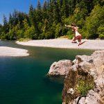 woman jumping into Chetco River