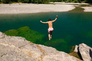 man jumping into Chetco River