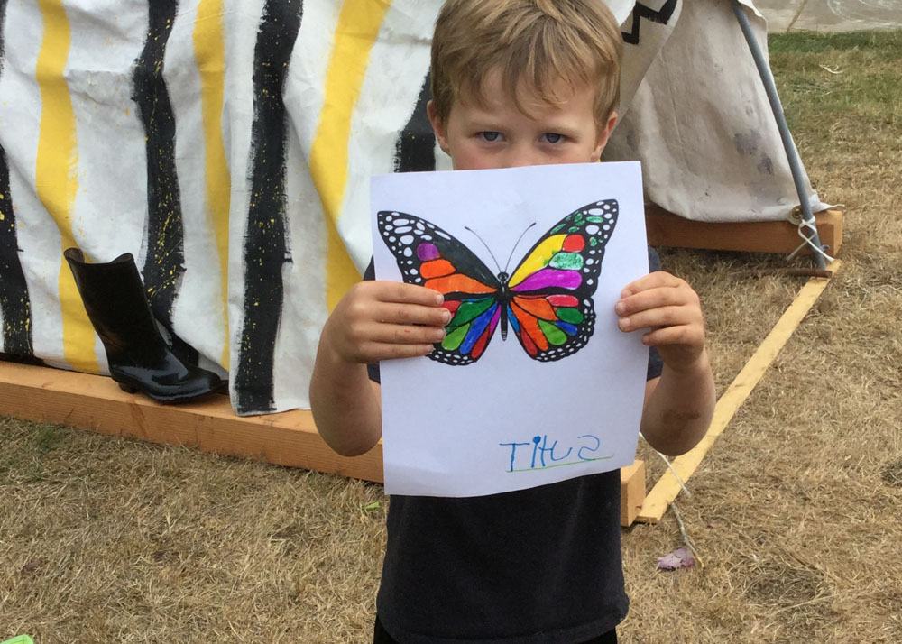 Child holding up drawing of butterfly