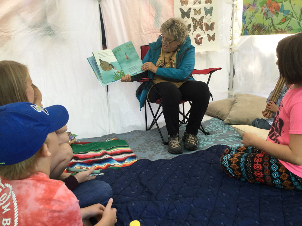 reading a book to children at monarch festival